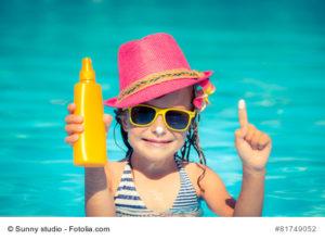 Foto Maedchen mit Sonnencreme im Wasser
