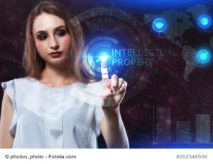 Junge Frau zeigt auf Schrift Intellectual porperty
