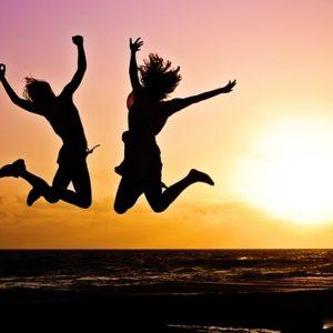 zwei Personen springen erfreut in die Luft